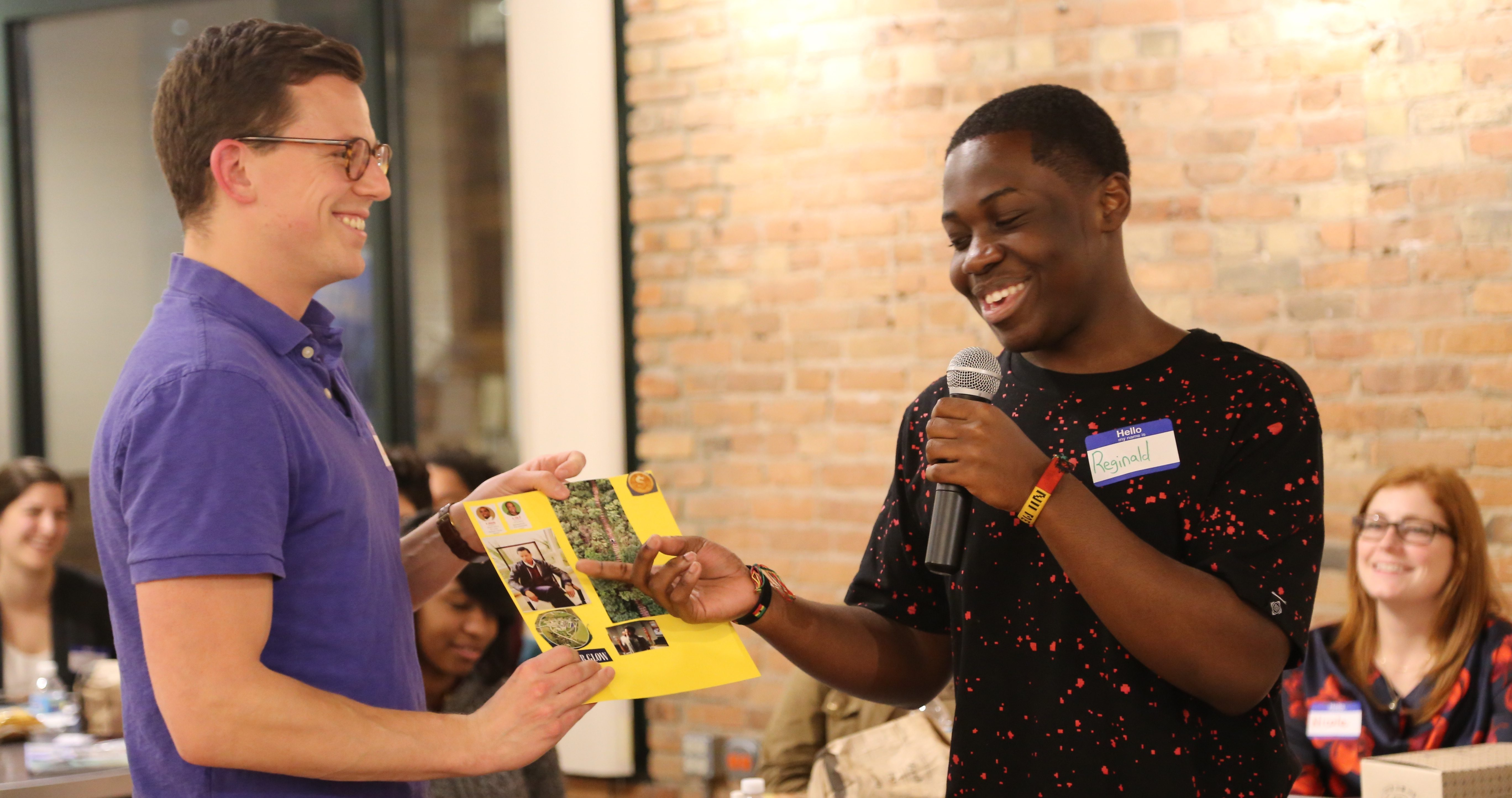 Volunteer. Our corporate mentor Chris helps teen Reginald share his vision  board with a group of peers.