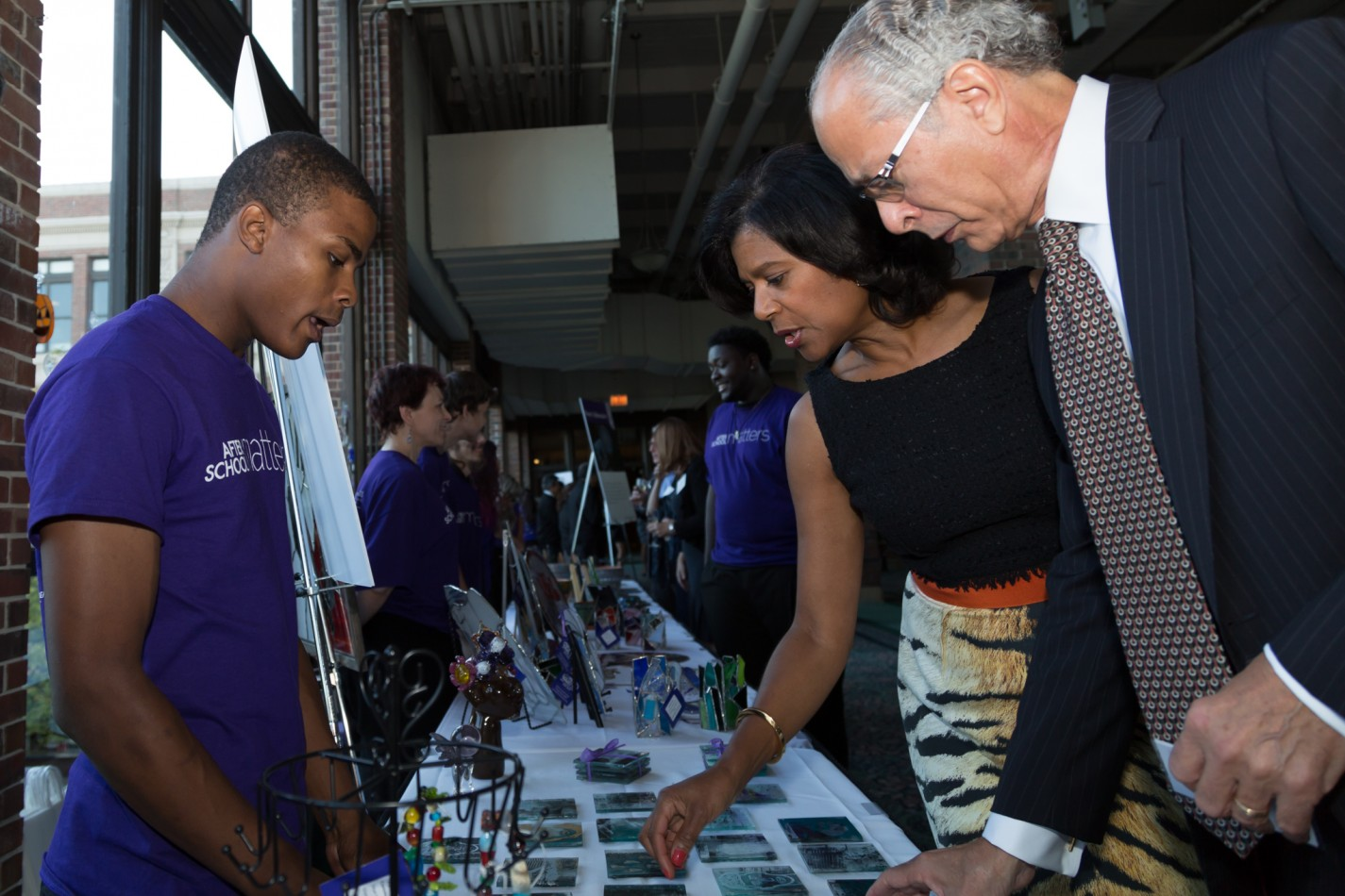 <p>After School Matters teen Alex H. in the Glassworks program shows his work to supporters during the reception of the After School Matters Annual Gala on September 21, 2015 at Navy Pier. Photo credit: Juan Martinez </p>
