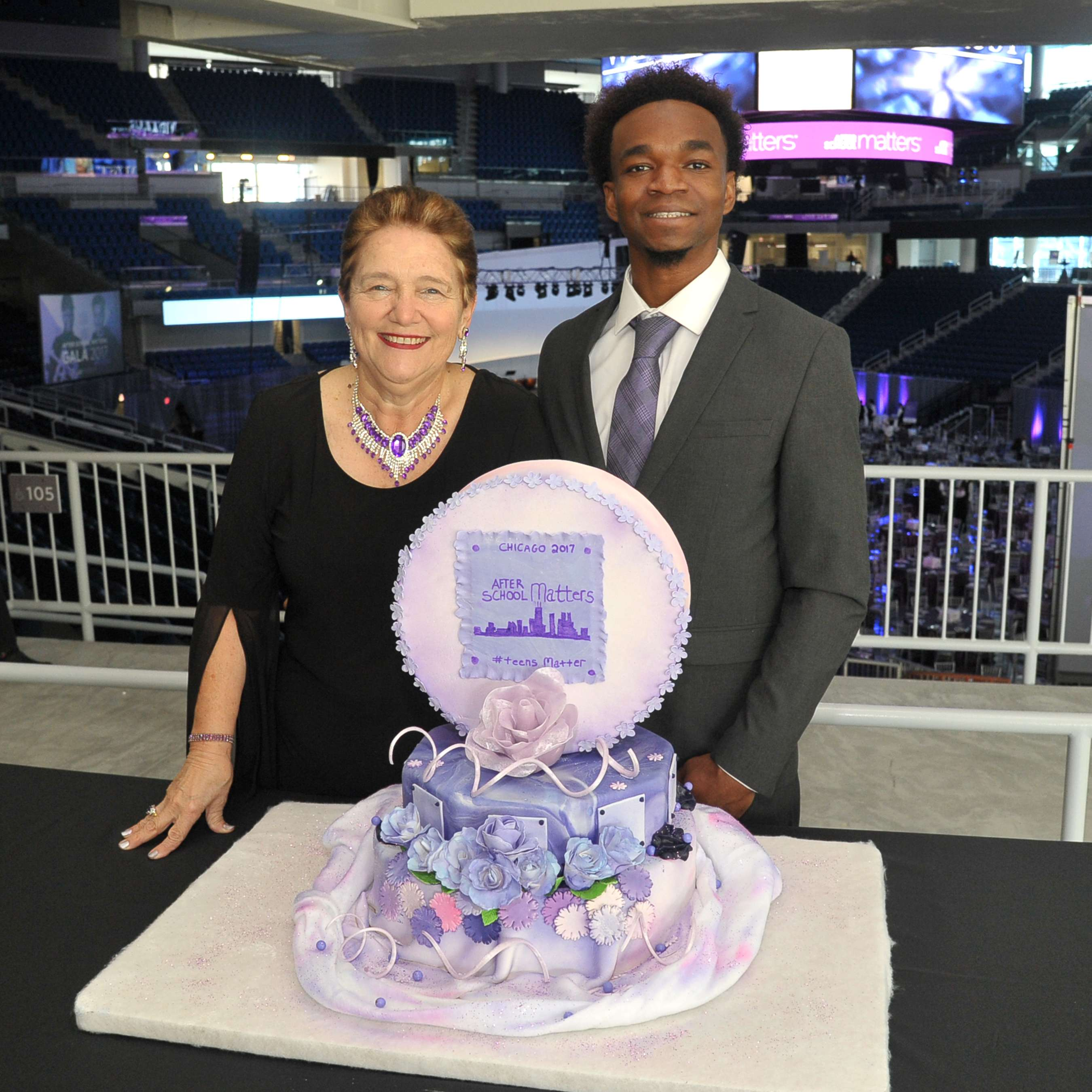 <p>After School Matters alumnus and current French Pastry School student Darrius Thomas (right) stands with his After School Matters instructor and life mentor Gloria Hafer (left) in front of a cake they decorated together for the After School Matters Annual Gala at Wintrust Arena on September 18, 2017. Photo credit: Dan Rest</p>