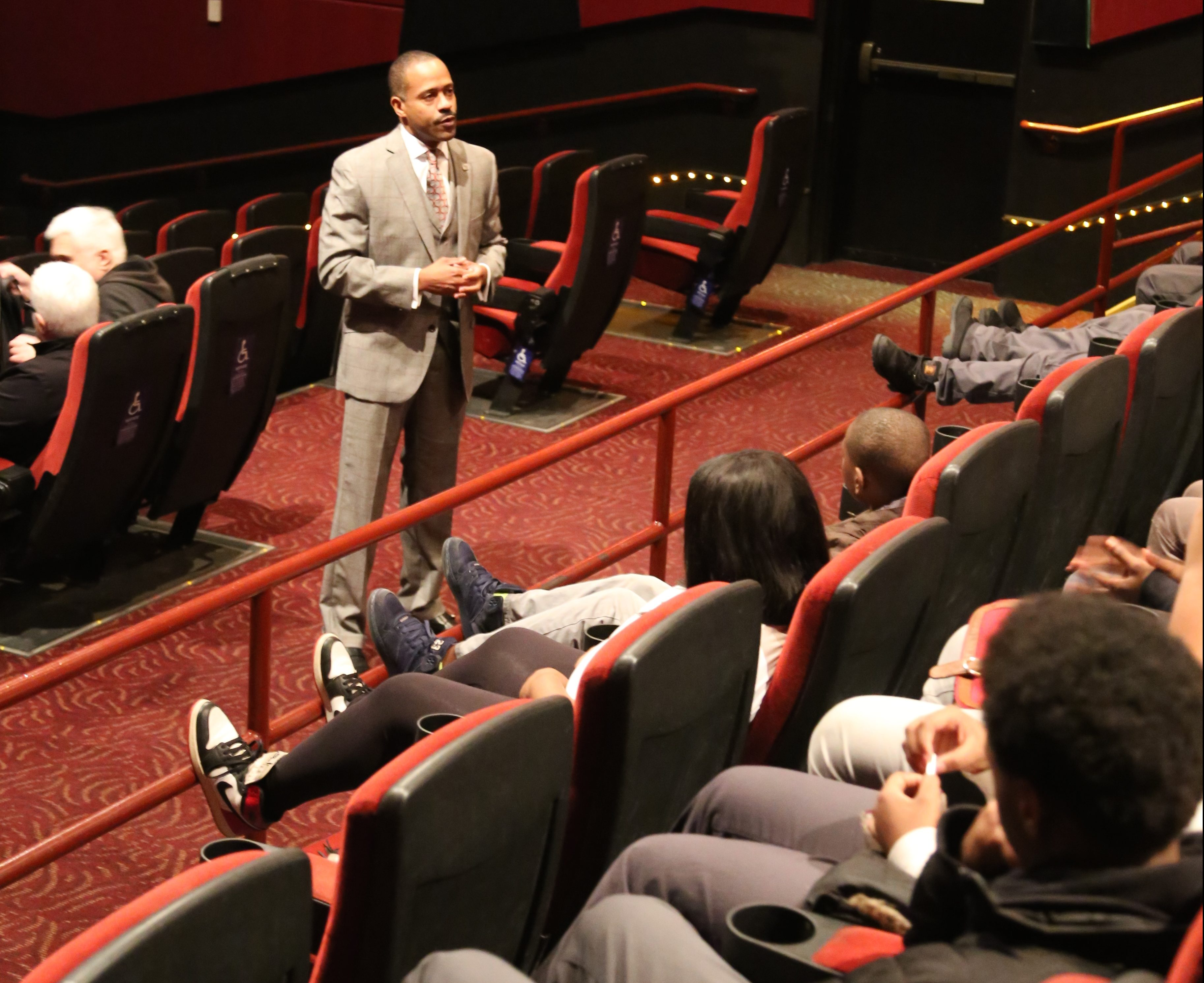 Image: Fifth Third Bank's Market President Eric S. Smith stands inside a movie theater speaking to two rows of teens in theater seats.