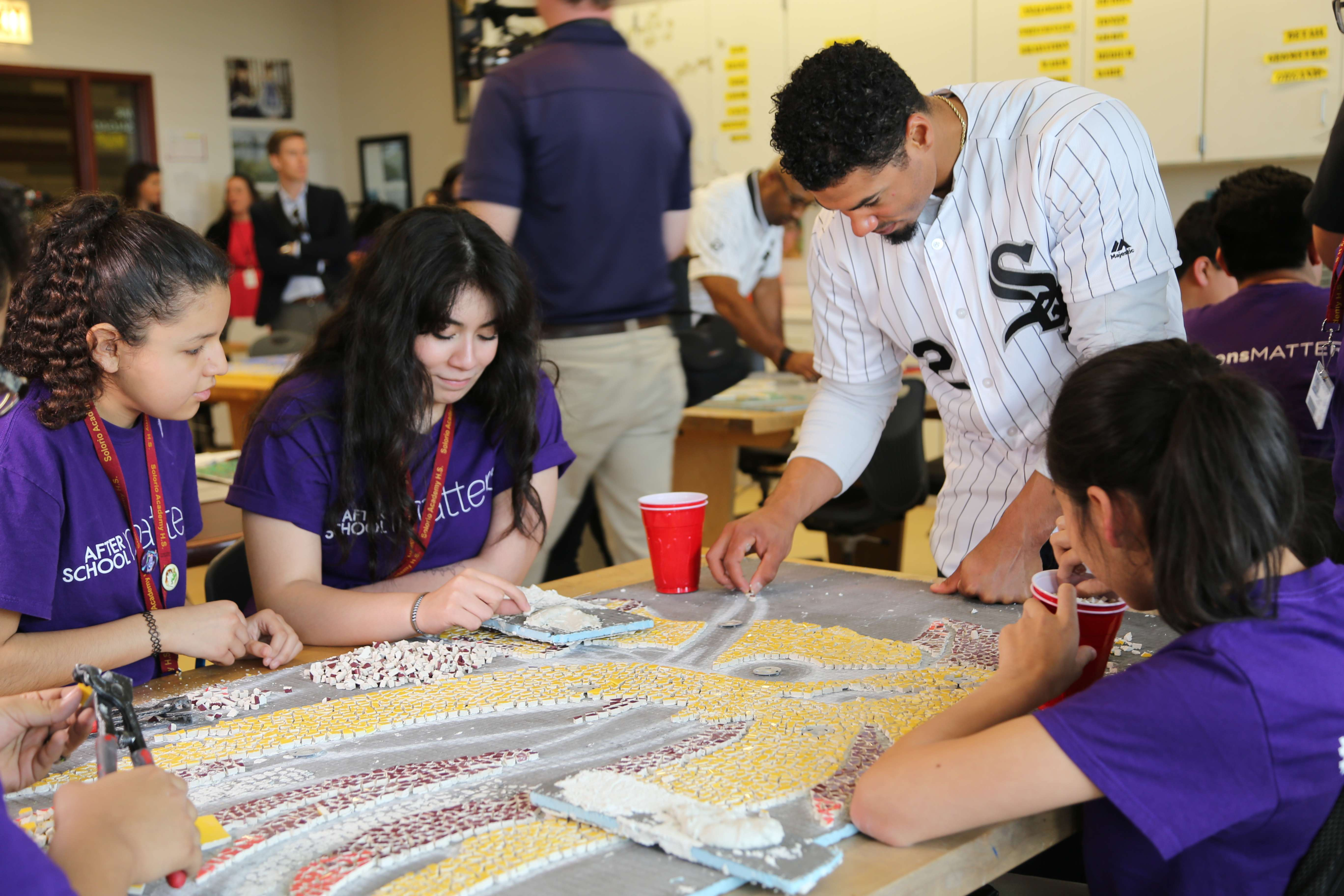 May works with teens in After School Matters to create a glass mosaic.