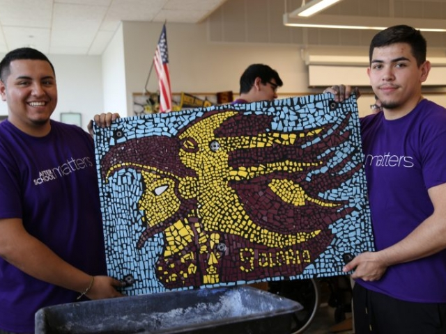 Juan and Victor hold up their finished piece: a sun warrior, the Solorio High School mascot.