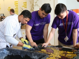May helps teens remove grout from a finished mosaic.